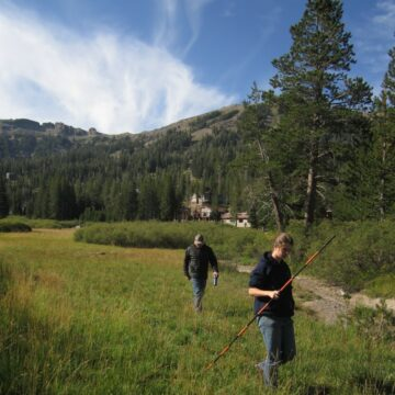 Two people walk across a meadow with measuring sticks, the Sierra mountains visible behind them.