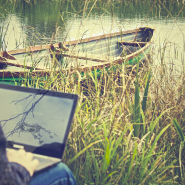laptop in a field with boat in the background