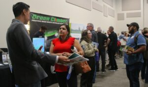A Latino man in a suit and a Latina woman in a red shirt talk in the foreground while a crowd of various people mill about behind them, looking at posters and presentations