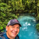 A smiling man in a baseball cap with a vivid blue lagoon and green plants in the background