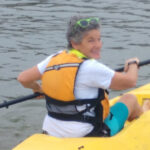 A woman with short gray hair sits atop a kayak with life vest and paddle